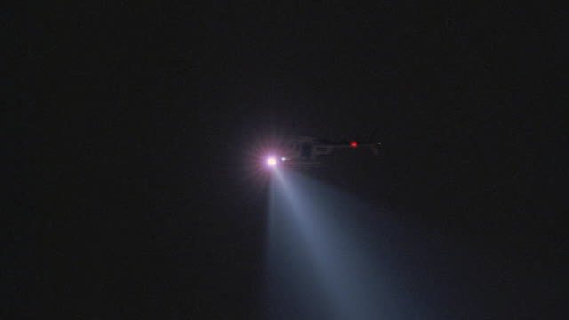 a police helicopter shines its searchlight across a dark sky. - searchlight stock videos & royalty-free footage