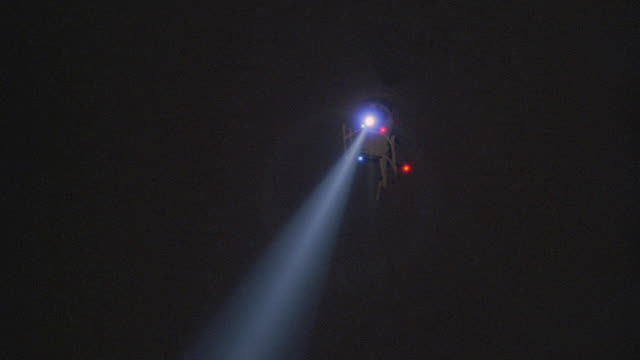 a police helicopter sweeps its searchlight above a neighborhood. - criminal investigation stock videos & royalty-free footage