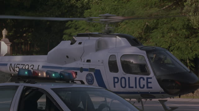 a police helicopter takes off near a police car parked in a neighborhood. - hubschrauber stock-videos und b-roll-filmmaterial