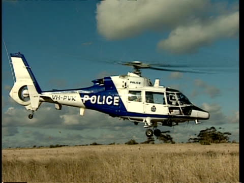 ms police helicopter taking off from field, flying away from camera - helicopter rotors stock videos and b-roll footage