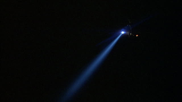 a police helicopter with a searchlight hovers above an industrial area. - searchlight stock videos & royalty-free footage