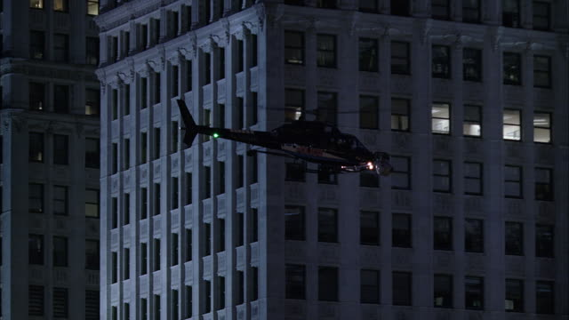 air to air police helicopter with searchlight flying near wrigley building at night / chicago, illinois, usa - wrigley building stock videos & royalty-free footage