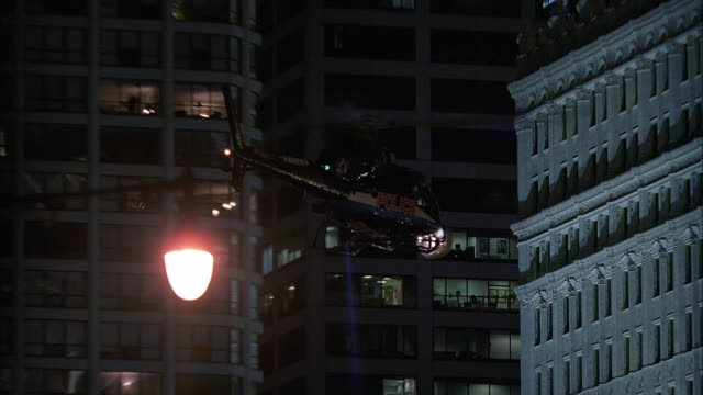 zi ms police helicopter with searchlight flying near wrigley building at night / chicago, illinois, usa - ornate stock videos & royalty-free footage