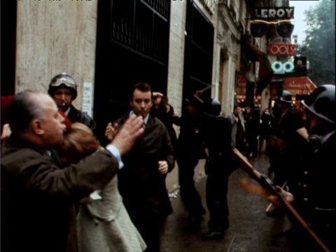 vídeos y material grabado en eventos de stock de police hit passing pedestrians walking past with end of rifles during student riots paris; may 68 - 1968