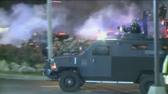 ktvi police in gas masks riot gear as ferguson protesters run from tear gas in the streets at night on august 17 2014 - st. louis missouri stock videos & royalty-free footage