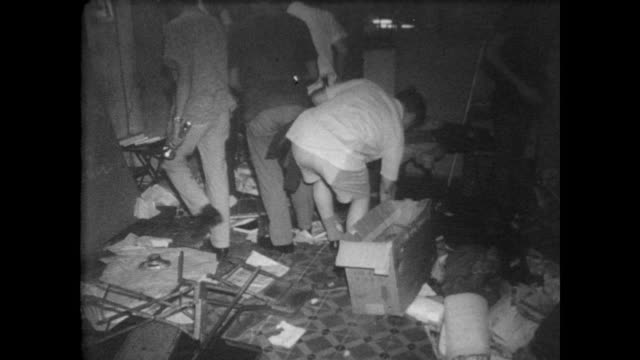 vidéos et rushes de police in hong kong searching buildings for explosives / bomb making equipment pulled out of ceiling / police escort crowd of suspects - 1967