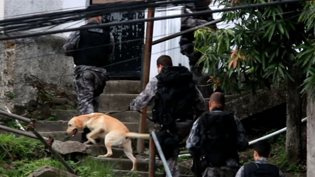 vídeos de stock e filmes b-roll de police in operations to clear favelas of drug gangs ahead of 2014 world cup brazil rio de janeiro ext military vehicles along towards helicopter... - favela