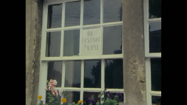 police in pilton during 1979 glastonbury festival and sign in pub window saying no festival people - shop window stock videos & royalty-free footage