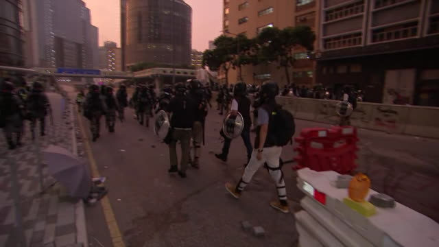 police in riot gear move through the streets of hong kong at dusk during a protest. - 盾点の映像素材/bロール