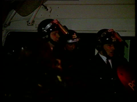 police in riot gear prepare for action during nighttime riot in brixton 1990 poll tax demonstrations 10 mar 90 - ブリックストン点の映像素材/bロール