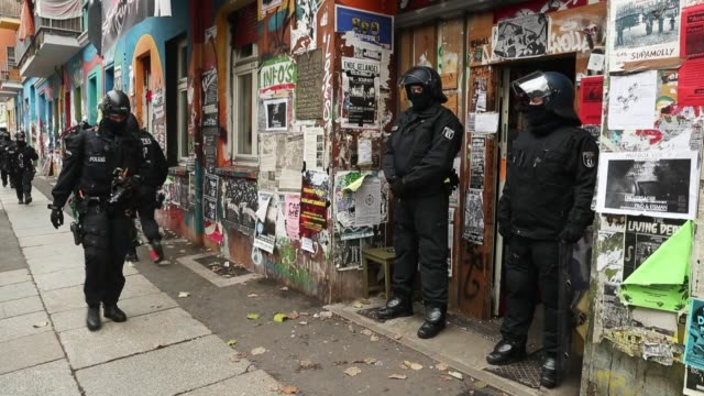 police in riot gear stand at the entrance to rigaer strasse 93 where colleagues had conducted a raid in an apartment earlier in the morning on... - aggression stock-videos und b-roll-filmmaterial