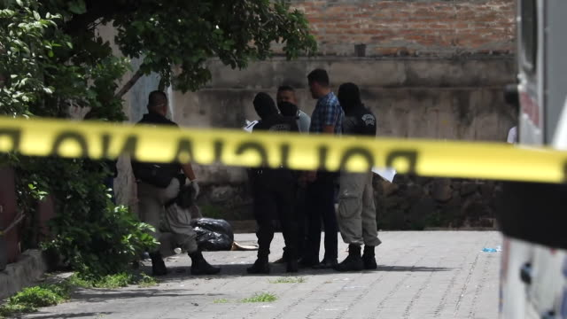 police in san salvador at murder scene deal with body dumped at side of road by gangs - ロープ仕切り点の映像素材/bロール
