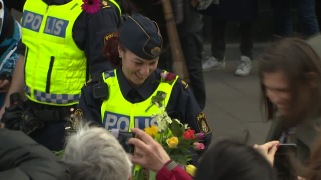 Police in Stockholm receiving flowers and applause as gratitude for their response to the lorry terror attack