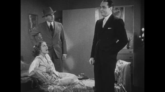 1931 police inspector (eddie kane) accuses joan crawford of stealing jewels but she shows him her dog and laughs at him - zurücklehnen stock-videos und b-roll-filmmaterial