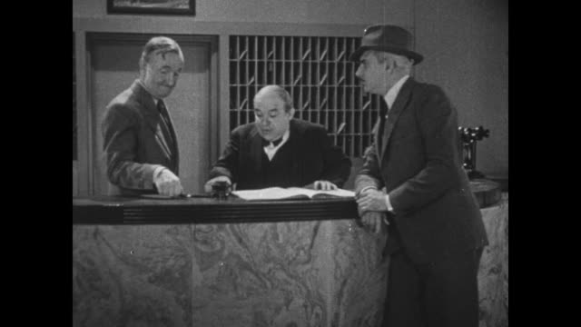 vídeos de stock e filmes b-roll de 1931 police inspector (eddie kane) questions two men behind hotel front desk, they answer in unison - 1931