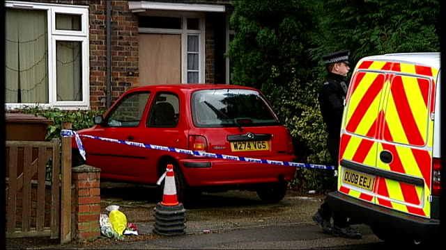 police investigate murder of babysitter in borehamwood; tx police cars parked in road policeman standing by cordoned-off driveway forensic officers... - ボーハムウッド点の映像素材/bロール