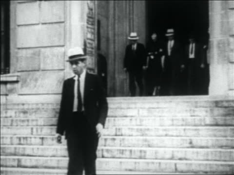 B/W 1933 police leading handcuffed woman down stairs