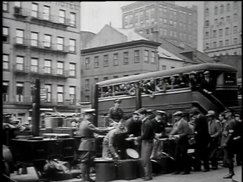 vídeos y material grabado en eventos de stock de police loading men onto a paddy wagon / men lining up for food / men eating with garbage cans for tables - 1934
