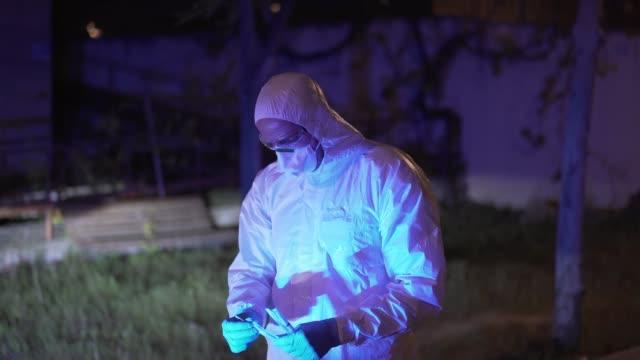 vídeos de stock e filmes b-roll de police man in anti-contagion clothing. fights the coronavirus. - vestuário para proteção