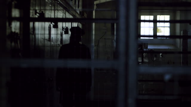 vidéos et rushes de police man lurking inside a jail - prison