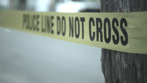 cu, shaky, r/f, police man stretching cordon tape around crime scene, staten island, new york city, new york state, usa - 犯罪 個影片檔及 b 捲影像