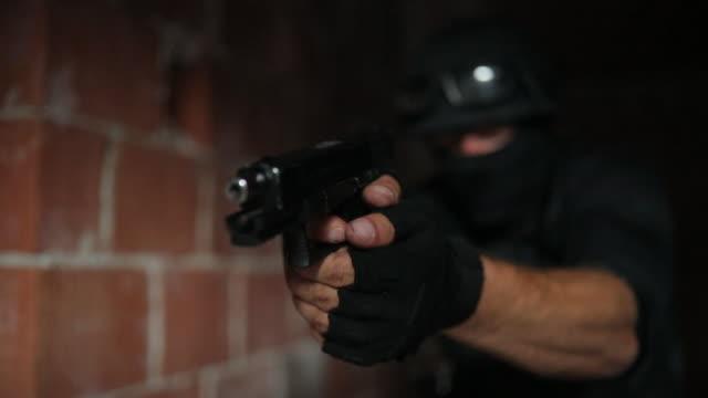 vidéos et rushes de homme de police avec une arme de poing - lunettes de protection