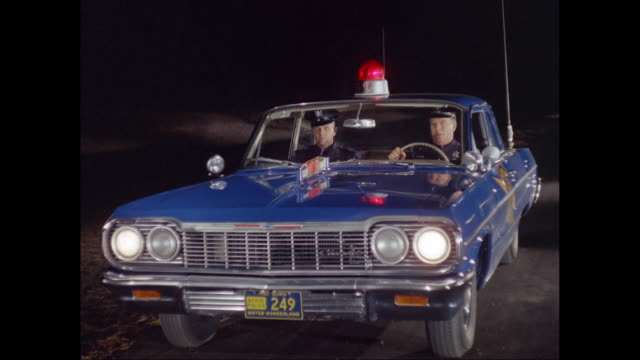 vidéos et rushes de ms police men getting out of car at night / united states - police