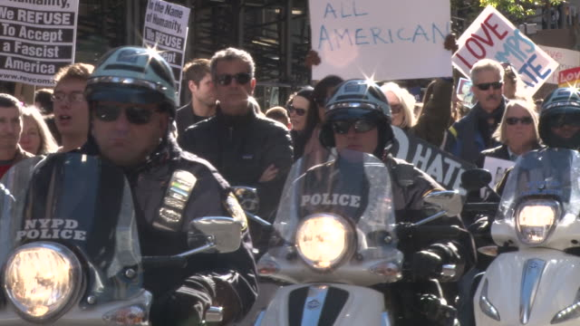 a police motorcade forms around the protesters as they ride north with the leaders of the march / various angles on the police line of motor scooters... - us republican party 2016 presidential candidate stock videos & royalty-free footage