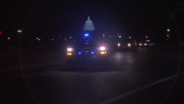 REAR POV Police motorcade with flashing emergency lights driving on Pennsylvania Avenue at night with U.S. Capitol Building beyond / Washington, D.C., United States