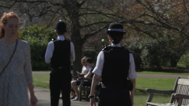 police move on people sitting and sunbathing in st james' park in central london as many flout the social distancing rules to enjoy the good weather... - police force stock videos & royalty-free footage