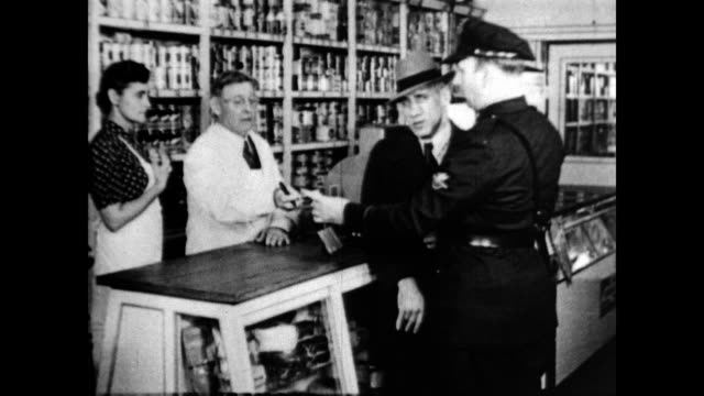 stockvideo's en b-roll-footage met / police officer apprehends man who tried to use counterfeit money in general store / man is handcuffed to police officer as he makes a call from... - geheime dienstagent