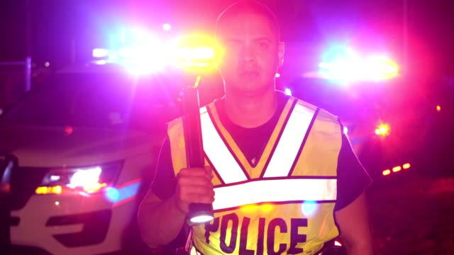 vidéos et rushes de officier de police pendant la nuit brille lampe de poche vers la caméra - un seul homme d'âge moyen