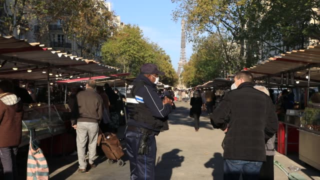 police officer checks the exit certificates of people at a food market during the first weekend of lockdown on october 31, 2020 in paris, france. the... - remote control video stock e b–roll