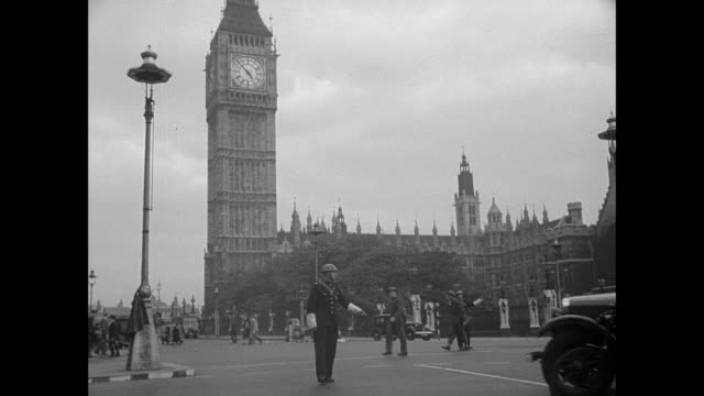 vídeos y material grabado en eventos de stock de ms a police officer directing vehicle and bicycle traffic near the tower of big ben / london, england, united kingdom - 1940