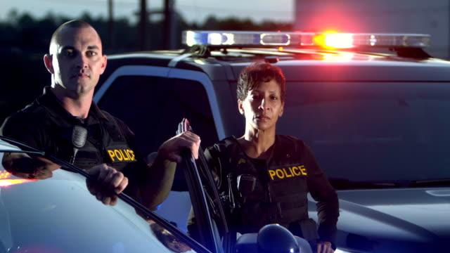 vidéos et rushes de un policier sort d'une voiture de patrouille et se tient aux côtés d'une policière - police