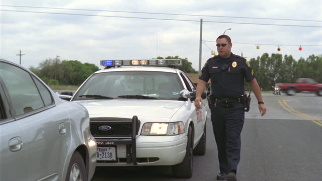 ws ms police officer getting out of police car and taking driver's license and vehicle registration from teen girl during traffic stop / elmendorf, texas, usa - driver's license stock videos and b-roll footage