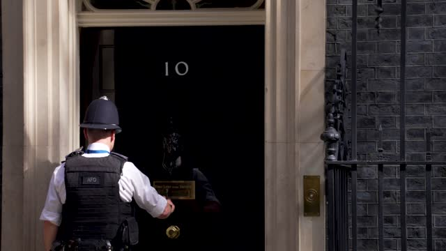 police officer goes in and out of downing street ahead of the state opening of parliament at downing street on may 11, 2021 in london, england. - politics and government stock videos & royalty-free footage