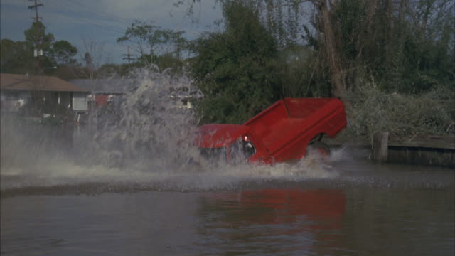 A police officer in a red truck crashes into a river.