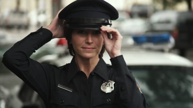 cu police officer looking around putting cap, smiling / dallas, texas, usa - see other clips from this shoot 1606 stock videos & royalty-free footage