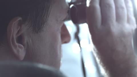 ecu, shaky, police officer looking through binoculars sitting in police van, staten island, new york city, new york state, usa - surveillance stock videos & royalty-free footage