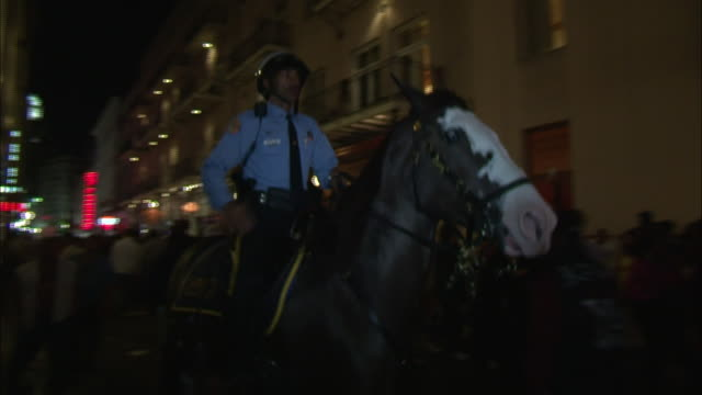 a police officer on horseback rides through a crowd on bourbon street. - bourbon street new orleans stock videos and b-roll footage