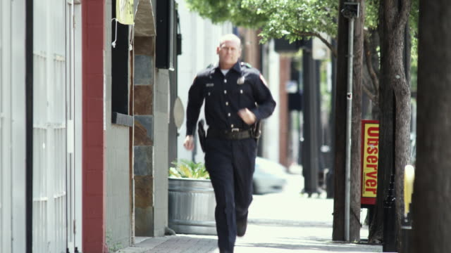 ws tu police officer running down sidewalk / dallas, texas, usa - see other clips from this shoot 1606 stock videos & royalty-free footage