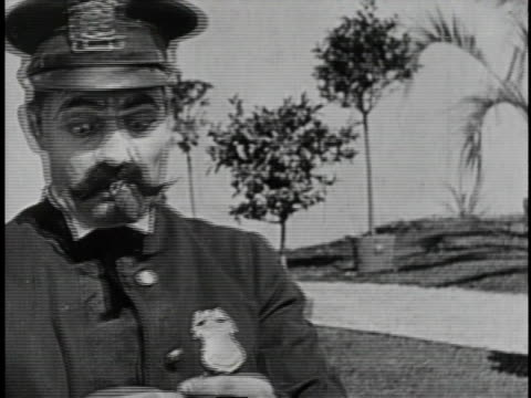 1920 b/w police officer smoking exploding cigar - sigaro video stock e b–roll