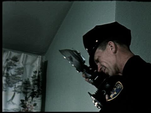 vídeos de stock, filmes e b-roll de 1965 ms police officer snapping flash photograph at crime scene/ oakland, california - photographing