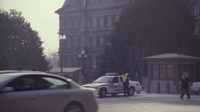 ws a police officer standing next to his service vehicle on the side of the road in front of an office building watching traffic pass / washington, district of columbia, united states - breitwandformat stock-videos und b-roll-filmmaterial
