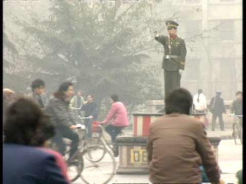 mwa police officer standing on pillar in busy road, directing traffic, china - surveillance stock videos and b-roll footage