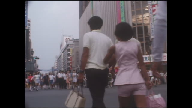 a police officer stands in the middle of ginza street as pedestrians walk by during the first day of the pedestrian paradise. - showa period stock videos & royalty-free footage