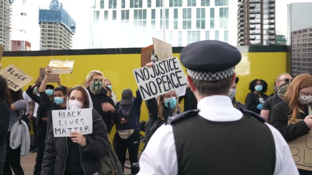 police officer stands next to black lives matter protesters in london on june 7, 2020 in london, united kingdom. the death of an african-american... - film stock videos & royalty-free footage