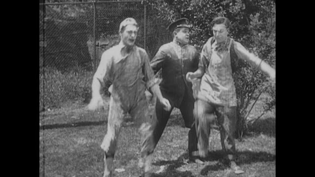 vídeos de stock e filmes b-roll de 1917 a police officer stops man (buster keaton) and the chef from fighting - maca