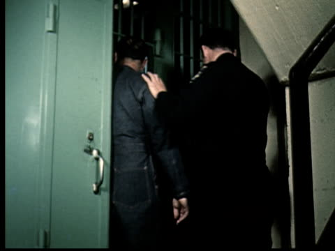 1965 ms pan police officer taking man to jail cell and locking him in - uniform stock-videos und b-roll-filmmaterial